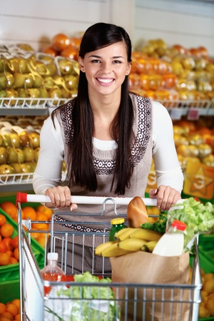 vegetables supermarket: Image of pretty woman with cart looking at camera Stock Photo