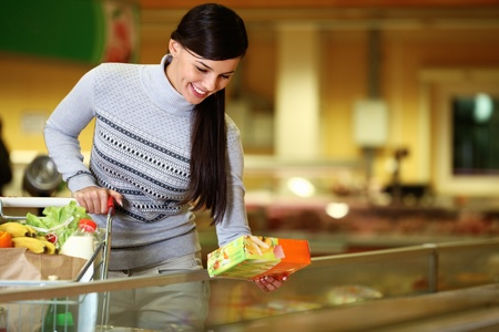 health food store: Image of pretty woman with cart choosing products in supermarket Stock Photo