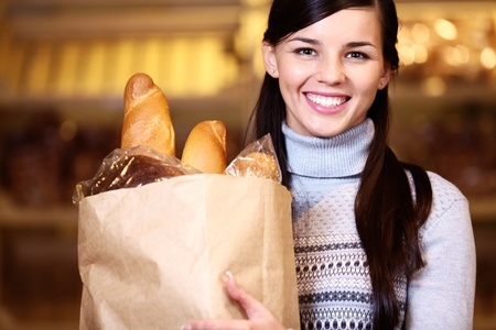 health food store: Image of pretty woman with pack of bread looking at camera