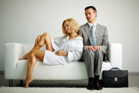 young woman sitting: Photo of man in suit sitting on sofa and looking at seductive woman near by