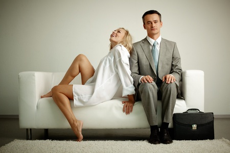 flirting women: Photo of serious man in suit sitting on sofa with seductive laughing woman near by