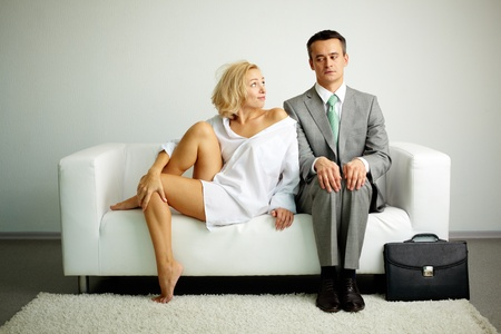 Photo of serious man sitting on sofa with seductive woman looking at him Stock Photo