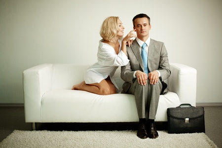 teasing: Photo of serious man sitting on sofa with seductive woman teasing him
