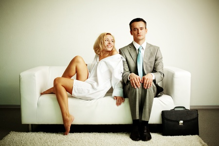 Photo of serious man sitting on sofa with happy seductive woman looking at him Stock Photo - 11268513
