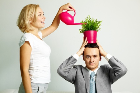Photo of serious man with plant on head being watered by happy woman photo