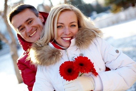 winter flower: Photo of happy man and woman outdoor in winter