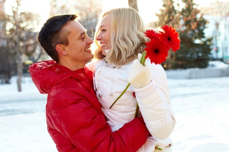 winter couple: Photo of happy man embracing pretty woman with herberas outdoor in winter Stock Photo