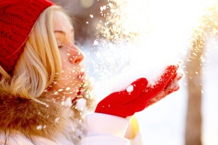 snow girl: Portrait of young woman holding snow on palms and blowing it