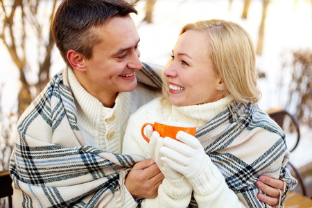 Photo of happy man and pretty woman with cups outdoor in winter photo