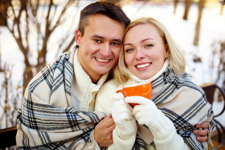 Photo of happy man and woman with cups looking at camera outdoors in winter Stock Photo