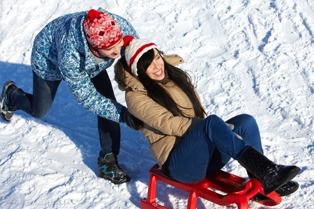 Portrait of happy couple tobogganing in winter  photo