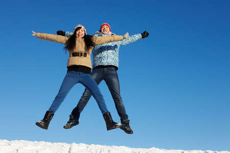 Portrait of happy couple in warm clothes jumping and looking at camera  photo
