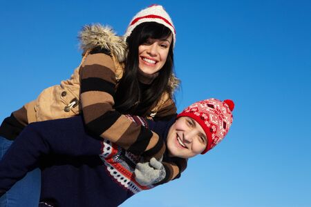 Portrait of happy couple in warm clothes looking at camera against blue sky photo