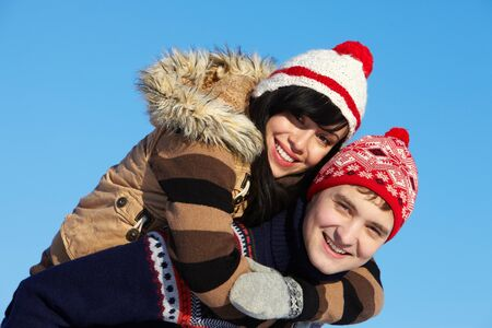 winterwear: Portrait of happy couple in warm clothes embracing and looking at camera