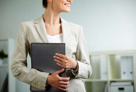 Close-up of businesswoman holding folder in hands photo
