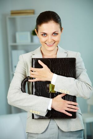 Portrait of smiling businesswoman with briefcase looking at camera in office photo