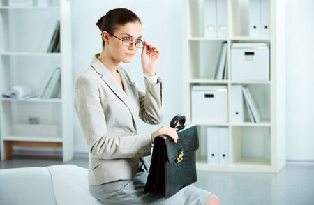 Portrait of serious businesswoman with briefcase sitting in office photo