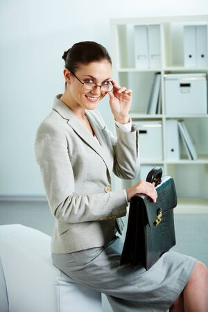 Portrait of successful female with briefcase looking at camera in office photo