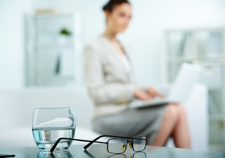 Close-up of workplace with glass of water and eyeglasses on it and businesswoman typing on background photo