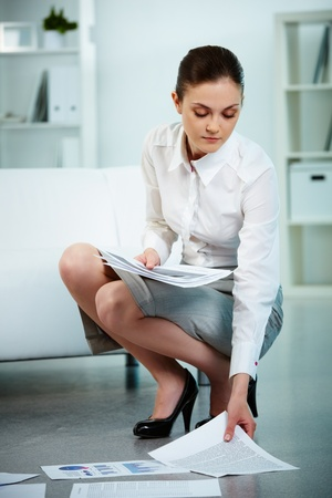 squatting: Portrait of serious businesswoman taking papers from the floor in office