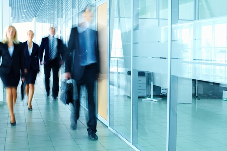 Blurred figures of business people walking along the corridor  Stock Photo