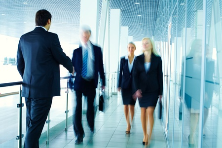 Business people meeting each other in the office corridor and shaking hands photo
