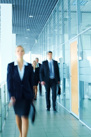 Business lady walking along the corridor ahead of her colleagues photo