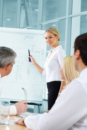 Pretty blonde presenting plan to her co-workers photo