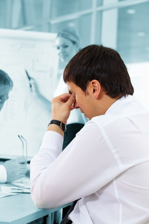 Businessman expressing tiredness during the meeting photo