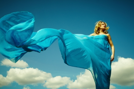 Young woman wrapped in a long piece of light fabric fluttering in the wind