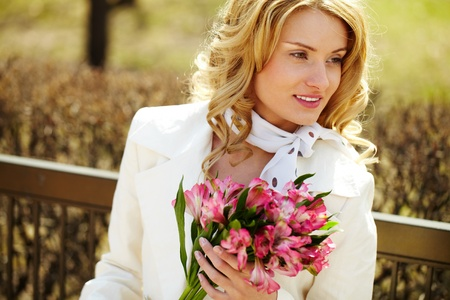looking away from camera: Pretty blond with a bouquet looking away from camera Stock Photo