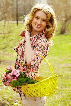 Girl holding a basket with flowers and looking at camera photo