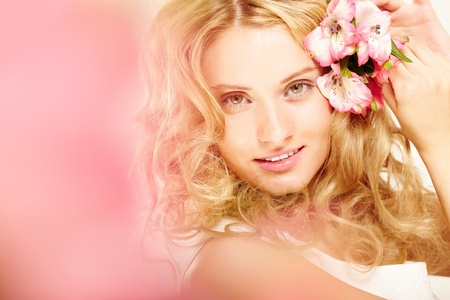 Charming blonde with fresh flowers in her hair photo