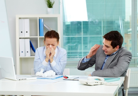 epidemic: Image of businesswoman sneezing while her partner looking at her unsurely in office  Stock Photo