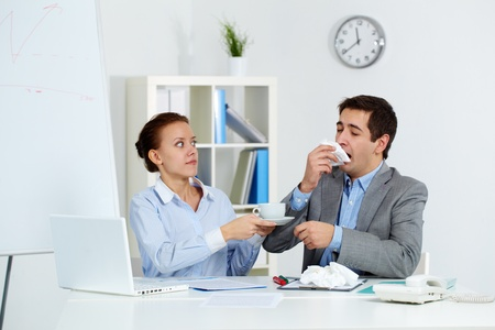 catarrh: Image of businessman sneezing while his anxious partner giving him a cup of tea in office