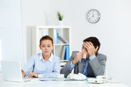 Image of sick businessman with tissue looking at laptop screen being pointed at by his colleague in office photo