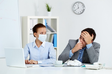 doku: Image of sick businessman with tissue looking at laptop screen with his colleague in mask sitting near by in office