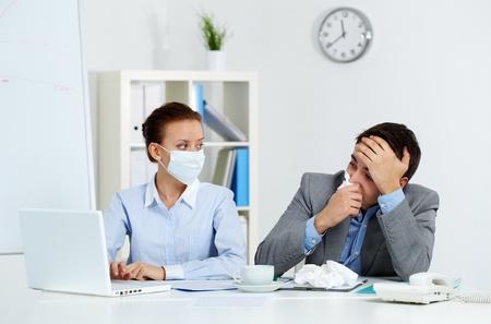 tejido: Imagen del hombre de negocios con el tejido enfermo mirando la pantalla del portátil con su colega en la máscara de estar cerca, en la oficina