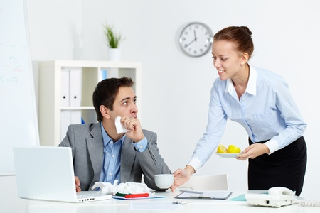 Image of sick businessman looking at his secretary giving him a cup of tea and lemon in office  photo