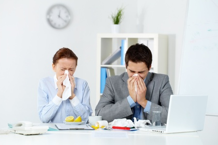 flu virus: Image of sick business partners blowing their noses in office  Stock Photo