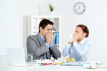 Image of sick business partners blowing their noses in office  Stock Photo - 11425784