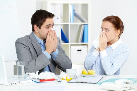 catarrh: Image of sick business partners blowing their noses in office  Stock Photo
