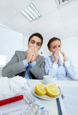 Image of sick business partners blowing their noses and looking at camera in office  photo