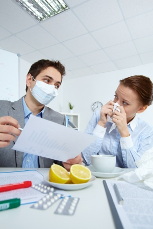 Image of man in mask looking at his sick business partner while discussing papers in office  photo