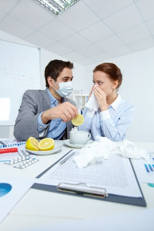 Image of sick businesswoman looking at her companion in mask offering her a cup of tea with lemon in office  photo
