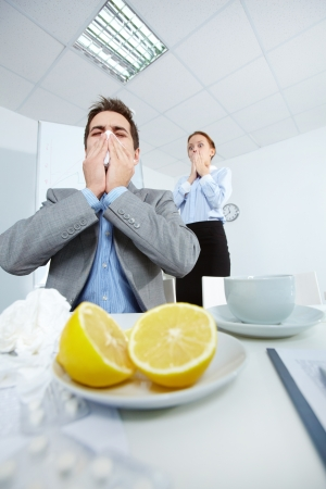 catarrh: Image of businessman sneezing while his partner on background looking at him with fright in office  Stock Photo