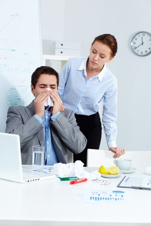 Image of ill businessman sneezing while his partner looking at him with care in office  Stock Photo - 11425781