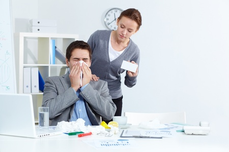 infect: Image of ill businessman sneezing while his partner offering him good medicine in office