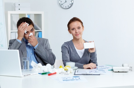 new medicine: Image of ill businessman blowing his nose while his partner showing new medicine Stock Photo