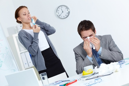 Image of businessman sneezing while his partner looking at him with fright in office  photo